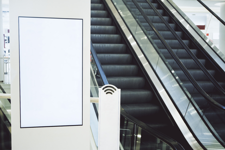 Close up of blank poster in shopping mall with escalator. Mock up Stock Photo
