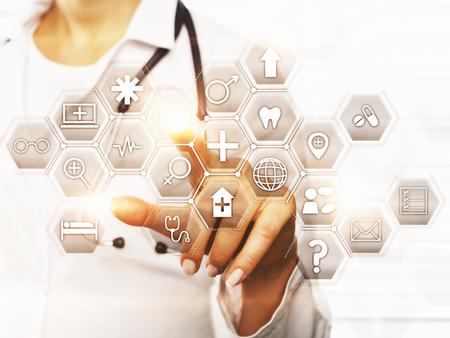 抽象デジタル アイコンを指している女医の手の正面。技術コンセプト