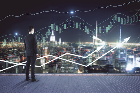 Young businessman on pier looking at night city with forex chart. Financial growth concept Stock Photo