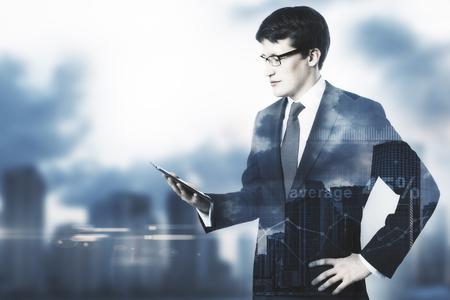 Attractive businessman using smartphone on blurry city background with copy space and business charts. Accountant concept. Double exposure