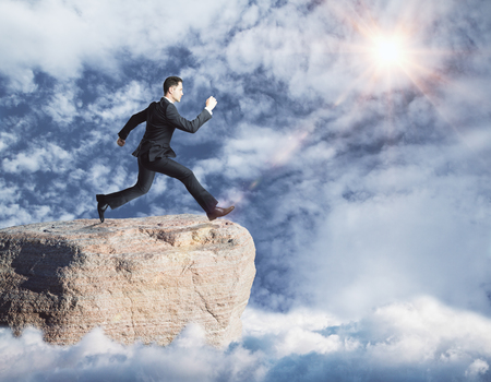 difficult lives: Side view of young businessman jumping off cliff on sky background. Risk concept