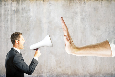 Hand gestures no to businessman screaming into megaphone on concrete background. Communication concept