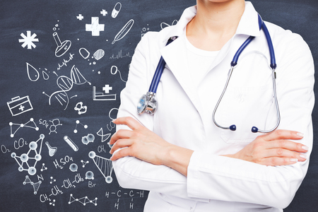 Young female doctor with stethoscope and folded arms standing on chalkboard background with drawings. Medicine concept