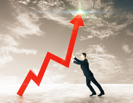 Side view of young businessman pushing red chart arrow on sky background. Toned image. Growth concept