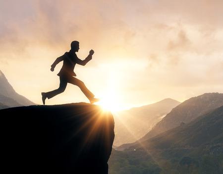 Backlit image of man silhouette jumping off cliff on landscape background. Motivation concept Standard-Bild