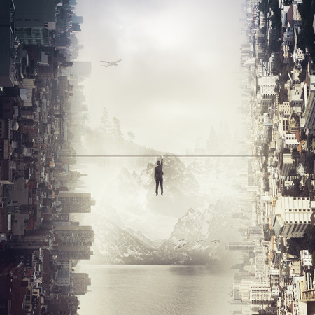 Back view of tiny businessman hanging on rope on abstract sideways city background. Risk concept