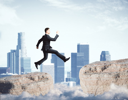 Side view of young businessman jumping from cliff on city background. Forward concept
