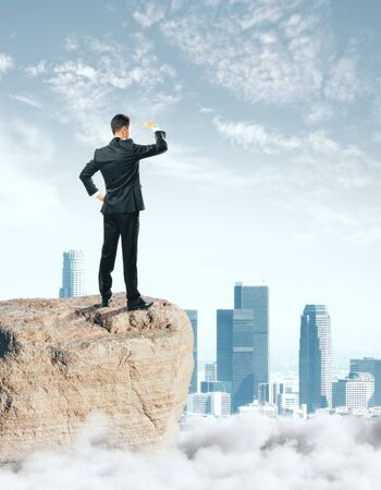 Businessman standing on rock and looking into the distance on city background. Future concept