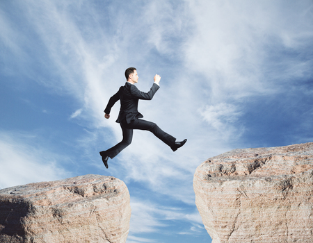 Side view of young businessman jumping from cliff on sky background. Faith concept