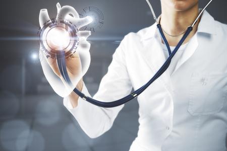 Jonge Kaukasische vrouwelijke doctop met behulp van stethoscoop op abstract digitaal hart in wazig kantoor interieur. Chirurg concept. 3D-rendering