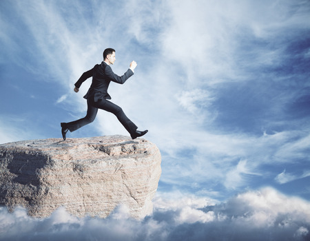 Side view of young businessman jumping off cliff on sky background. Success concept