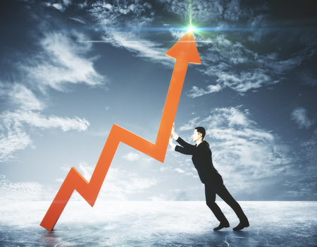 Side view of young businessman pushing red chart arrow on sky background. Success concept