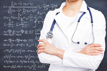 Young female doctor with stethoscope and folded arms standing on chalkboard background with formulas. Science concept Stok Fotoğraf - 81099718