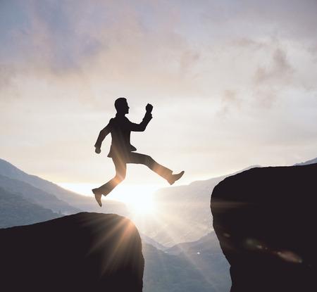 風景の背景に崖から飛び降りる男シルエットの逆光。測定概念