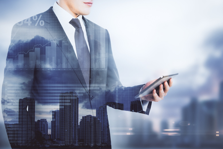 Businessman using cellphone on blurry city background with copy space and business charts. Technology concept. Double exposure