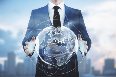 Businessman holding abstract digital globe on blurry city background. Communication concept. Double exposure 스톡 콘텐츠