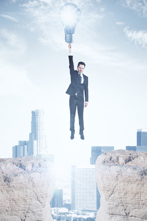 Flying businessman with lamp on light city background. Enlightenment concept