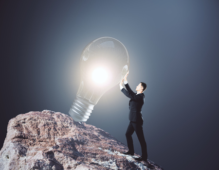 Side view of young businessman on rock hill holding glowing light bulb. Grey background. Success concept. 3D Rendering