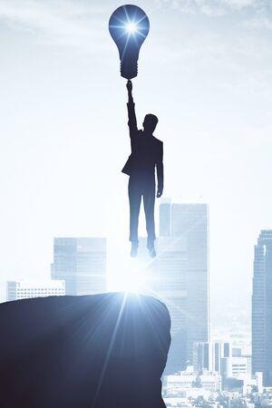 ランプを光市の背景に飛んでいる実業家の逆光。クリエイティブのコンセプト