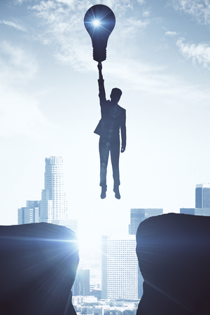 Backlit image of flying businessman with lamp on light city background. Creative ideas concept