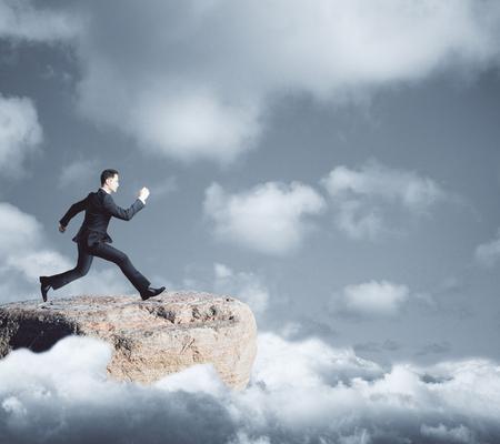 무딘 하늘 배경에 격차를 향해 실행 산 위에 젊은 사업가의 측면보기. 위험 개념 스톡 콘텐츠