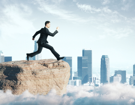 Side view of young businessman jumping off cliff on city background. Hope concept Stock Photo