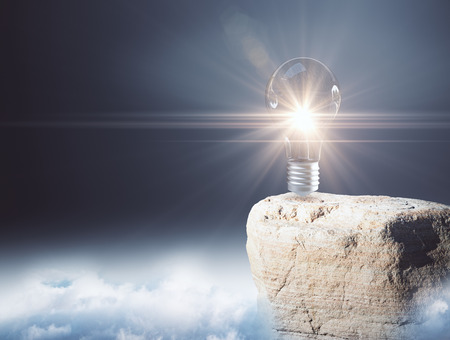 Illuminated light bulb on mountain top. Dull sky background. Genius concept. 3D Rendering