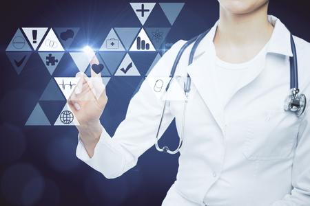 女医は暗い青色の背景にデジタル医療アイコンを指します。デジタル化の概念