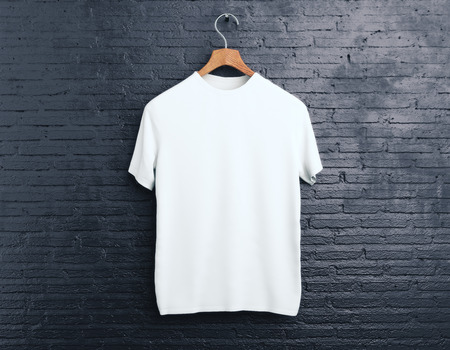 Wooden hanger with empty white t-shirt hanging on dark brick background. Shopping concept. Mock up. 3D Rendering