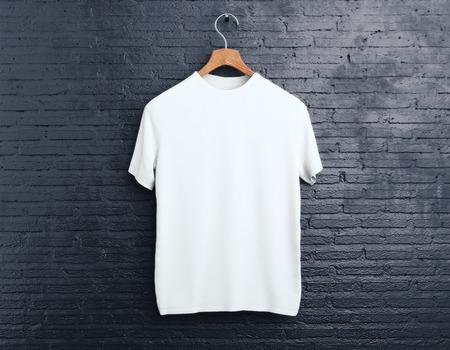 Percha de madera con camiseta blanca vacía colgando sobre fondo de ladrillo oscuro. Concepto de compras. Bosquejo. Renderizado 3D