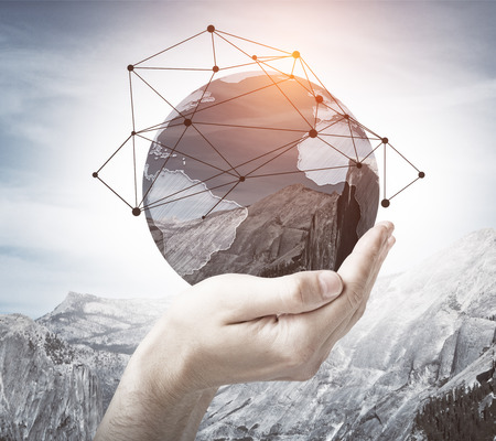 Male hand holding abstract globe with mountains and polygonal pattern on sky background. Global networking concept. Double exposure. Elements of this image furnished by NASA