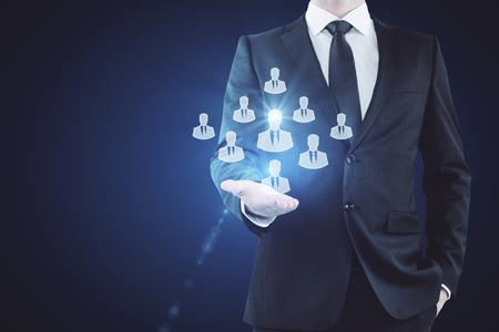 Businessman holding HR hologram on dark background. Employer concept Stok Fotoğraf - 81792265