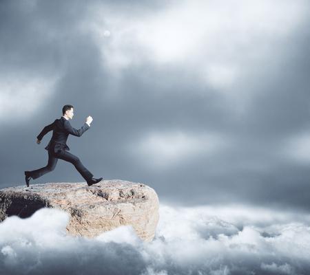鈍い空を背景にギャップに向かって山トップ ランニングの青年実業家の側面図です。リスクの概念