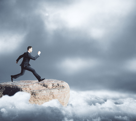 overcome: Side view of young businessman on mountain top running towards gap on dull sky background. Risk concept