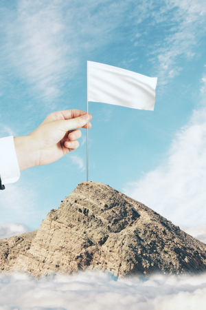 Hand placing flag on mountain top on sky background. Winning concept