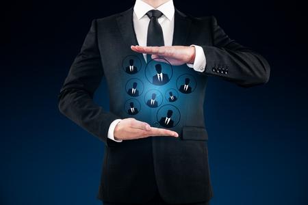 Businessman holding glowing HR hologram on dark blue background. Employment concept Stok Fotoğraf - 81792363