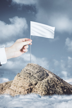 Hand placing flag on mountain top on sky background. Victory concept