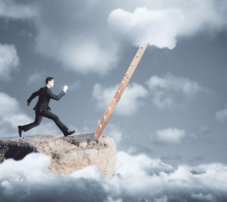 무딘 하늘 배경에 사다리를 향해 실행 산 상단에 젊은 사업가의 측면보기. 성장 컨셉