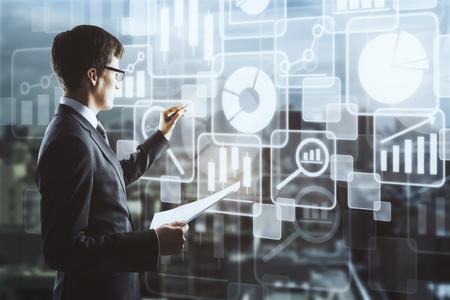 Zijportret van knappe zakenman met document in hand tekening abstracte digitale business charts en pictogrammen geprojecteerd op onscherpe stad achtergrond. Analytics-concept. Dubbele blootstelling
