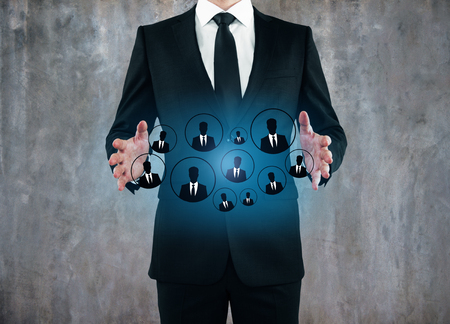 Businessman holding glowing HR hologram on concrete wall background. Recruiting concept