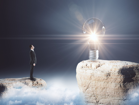 Side view of young businessman on mountain top looking at glowing lamp. Grey background. Creativity concept. 3D Rendering