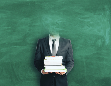 Headless businessman with books on chalkboard background. Education concept