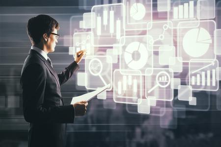 Zijportret van knappe zakenman met document in hand tekening abstracte digitale business charts en pictogrammen geprojecteerd op onscherpe stad achtergrond. Financieringsconcept. Dubbele blootstelling
