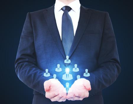 Businessman holding HR hologram on dark background. Recruiting concept Stok Fotoğraf - 81795117