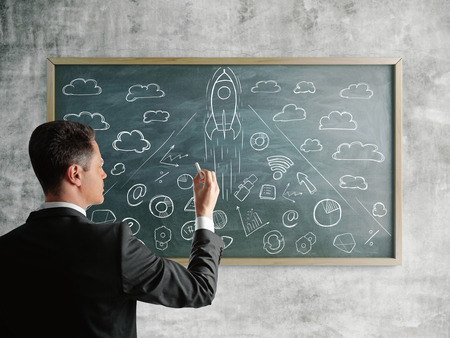 Young businessman drawing spaceship on blackboard hanging on textured concrete wall. Entrepreneurship and startup concept. 3D Rendering