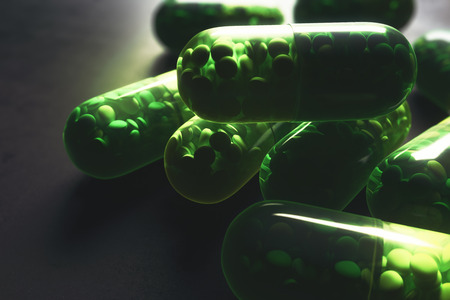 Close up of green pill capsules on concrete background. Medicine, prescription drugstore concept. 3D Rendering