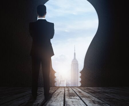 Back view of thoughtful young businessman standing in abstract room with light bulb opening, city view and daylight. Success concept. 3D Rendering