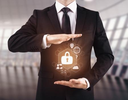 Zakenman die abstract gloeiend cybersecurityhologram in onscherp bureaubinnenland houden. Internetbeveiliging en innovatieconcept. 3D-weergave
