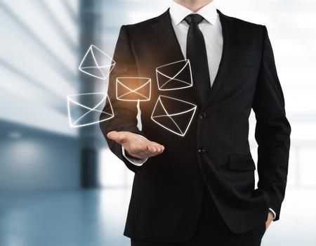 흐릿한 인테리어에 빛나는 디지털 편지를 들고하는 사업가. 이메일 네트워킹 개념. 3D 렌더링 스톡 콘텐츠