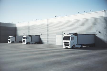 Facade of an industrial building and warehouse with freight cars parked parallelly under bright blue sky. Advertising copy space. Transport concept. 3D Rendering